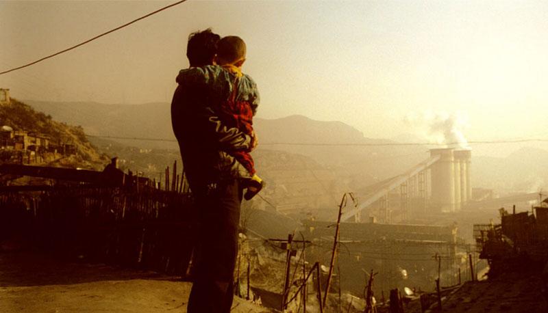 Schon bald Vergangenheit: Bergarbeiter mit Kind auf dem Arm am Rande einer chinesischen Kohlemine