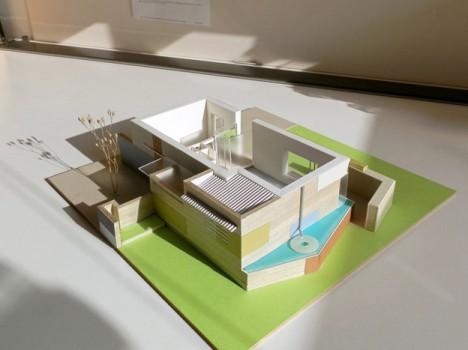 """Passivhaus für einen Single-Haushalt. Die warme Aufenthaltszone ist auf 3 Seiten mit Nebenräumen, Wasserbecken und Hochbeeten """"eingepackt"""". (Entwurf und Modellfoto: © Irmgard Brottrager)"""
