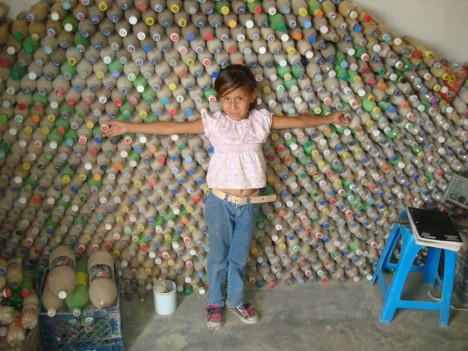 Mexikanisches Mädchen vor mit Erde gefüllten PET-Flaschen