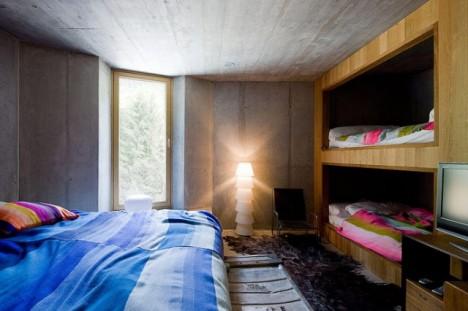 Eines der Schlafzimmer: Stein und Holz bringen die umliegende Natur ins Haus