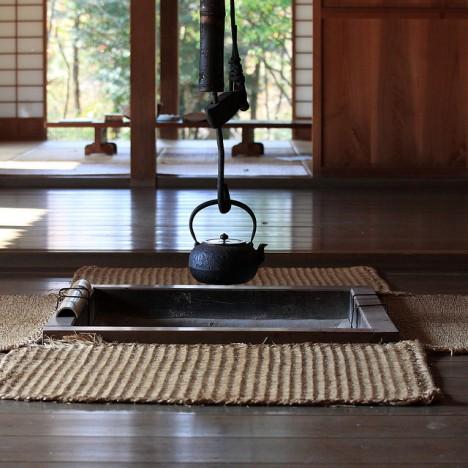 Schmiedeeiserner Teekessel an einer offenen Feuerstelle in einem traditionellen japanischen Haus