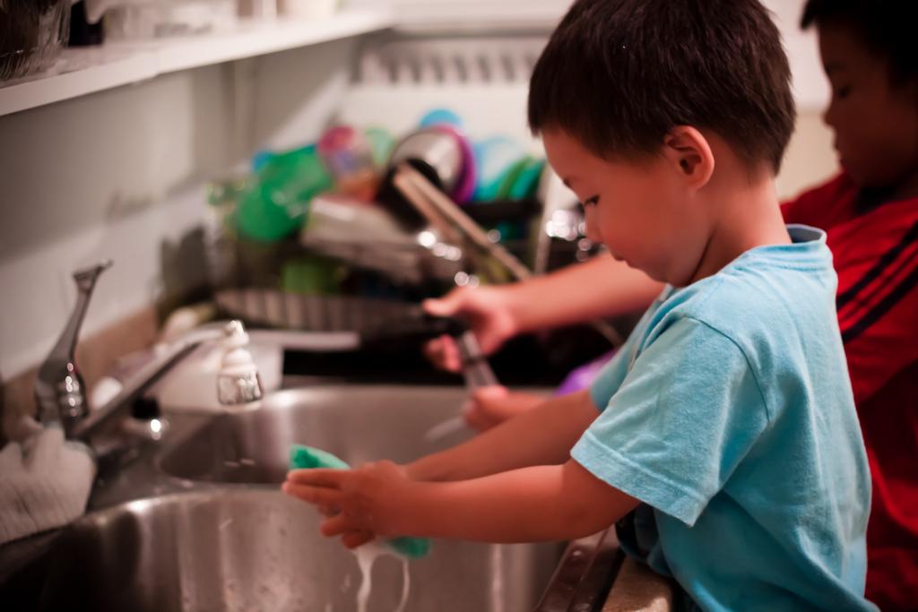 Kinder beim Geschirr abwaschen