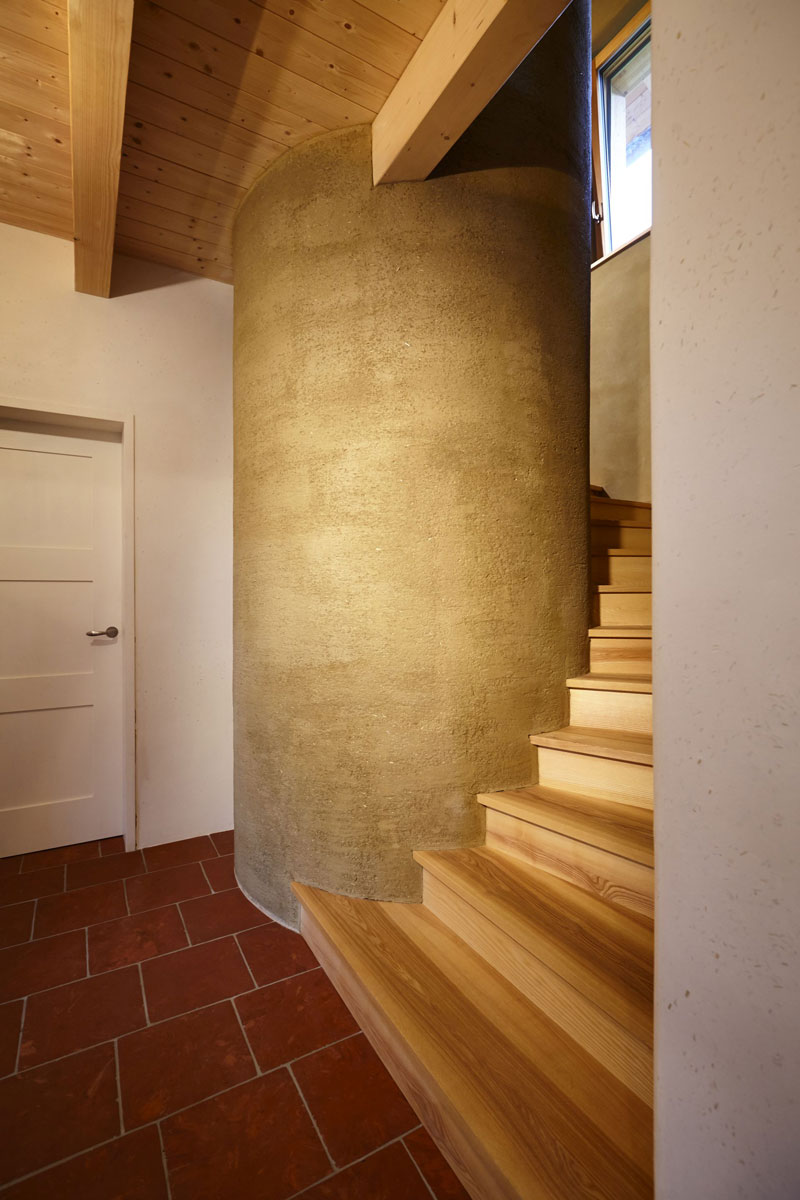 Um den fünf Meter hohen, mit Lehm verputzten Wärmespeicher schlängelt sich die Treppe in das Obergeschoss. Der Solartank speichert die Wärme von den Solarkollektoren und dem Holzkessel.