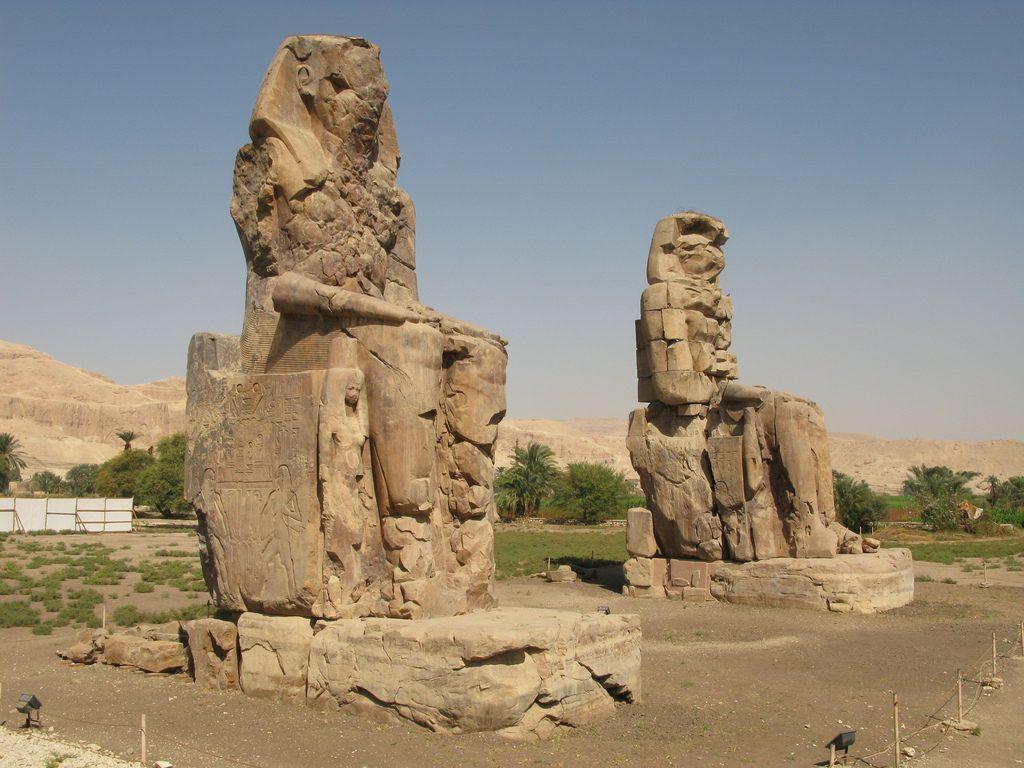 Die Kolosse von Memnon sind zwei ägyptische Giganten. Links in Kniehöhe sieht man eine wesentlich kleinere menschliche Figur und im Sockel noch kleinere Menschen. Foto (C) Silke Baron / flickr CC BY 2.0